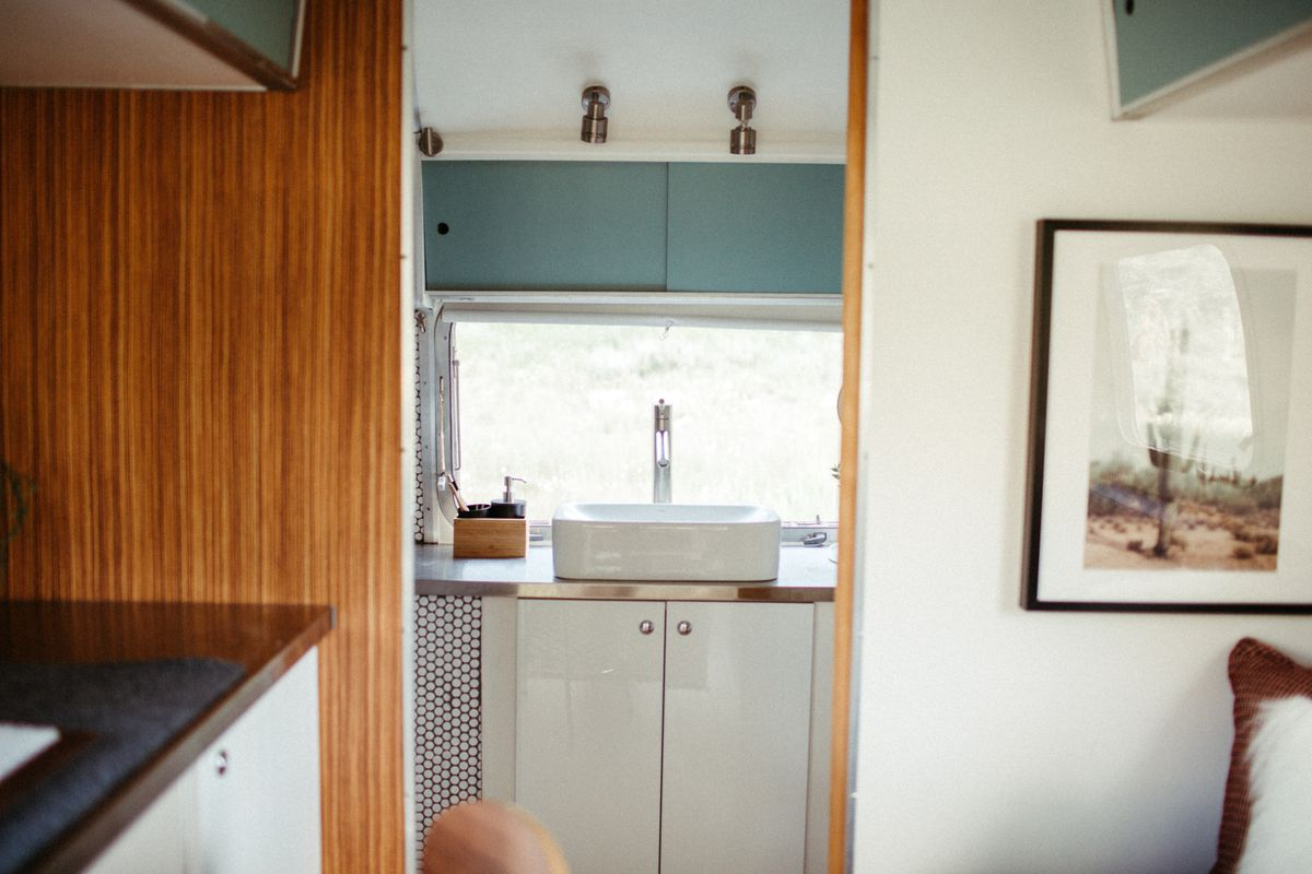 A look at the rear area of the trailer which has a bathroom with white sink and white cabinets.