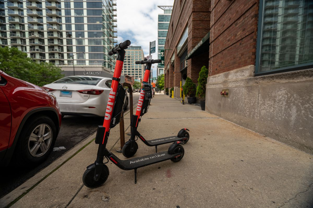 Two scooters parked on a sidewalk next to a brick building and two parked cars.