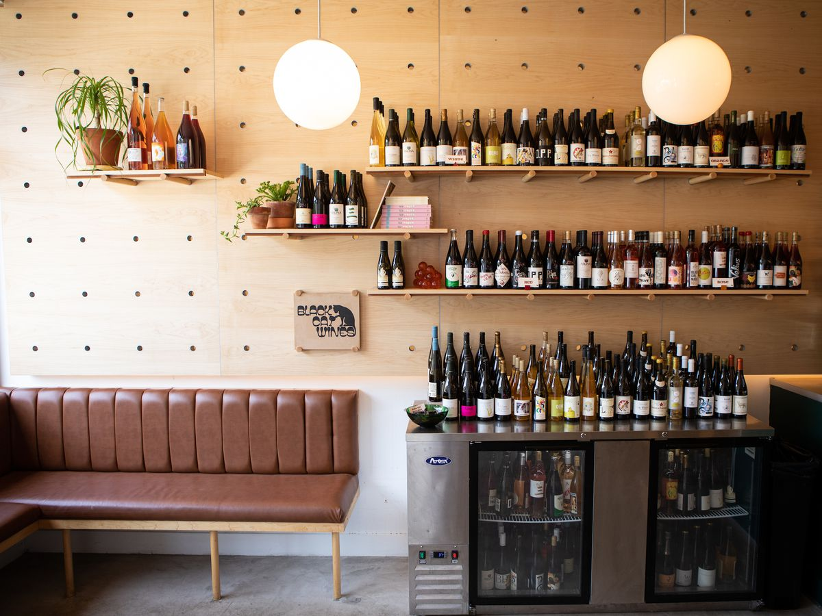 A maple wood wall lined with moveable shelves filled with wine bottles sit over a low refrigerator filled with wine and a brown banquette to the left
