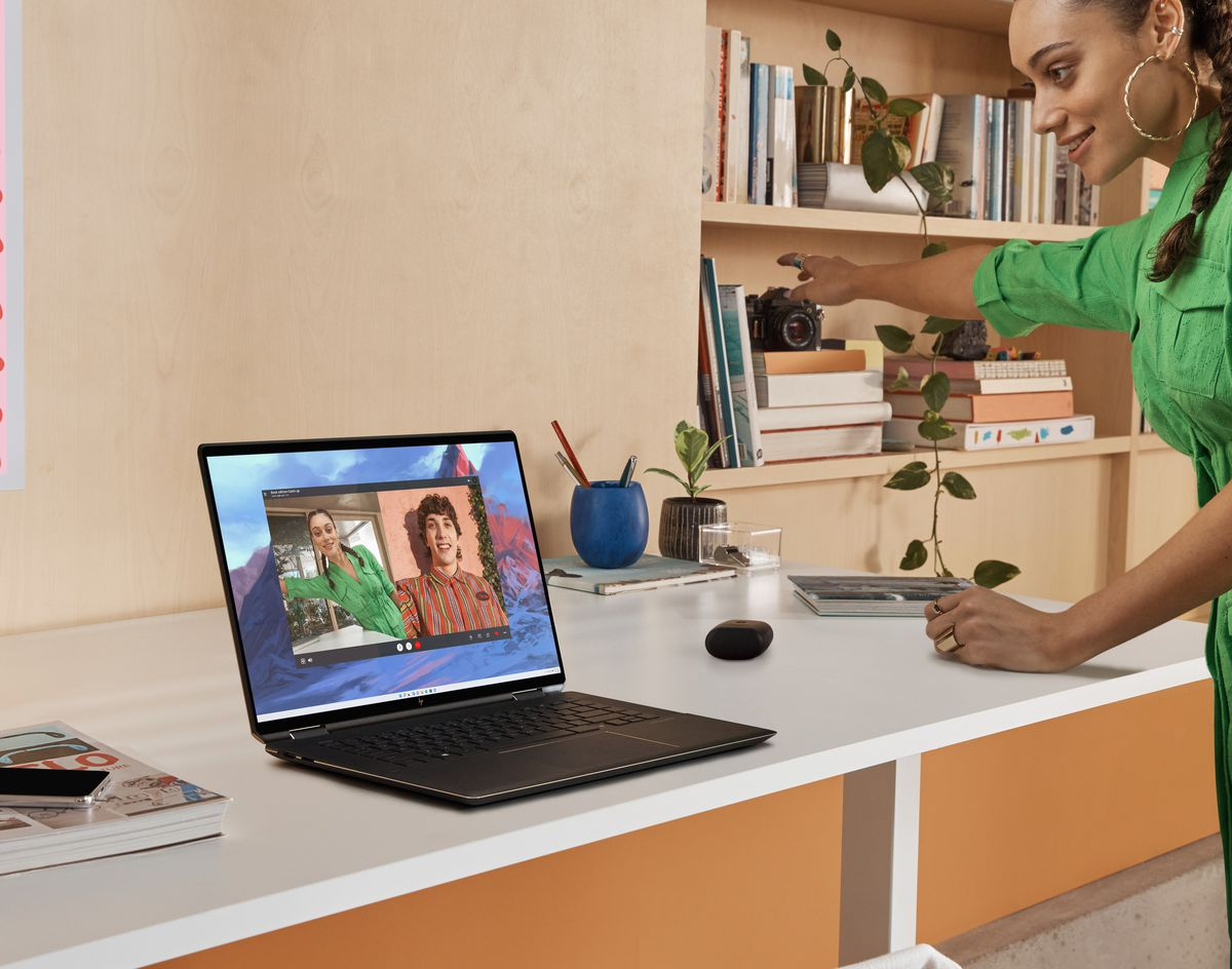 A user participates in a video call on the HP Spectre x360 16, pointing to the right. The laptop sits on a white desk. To its left are a book and a smartphone. To its right are a small potted plant, an earbuds case, a pencil case, and a full bookcase.
