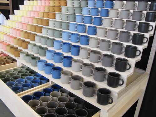 Shelves and drawers full of ceramic mugs arranged by color.