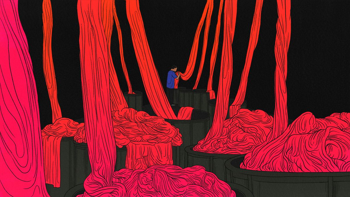A lone worker surrounded by yards and yards of dyed red cloth.