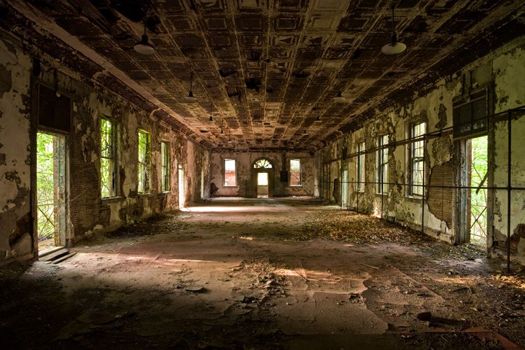 The interior of the Hart Island Women's Asylum. The room is large and in a state of decay with peeling paint and stripped wood.