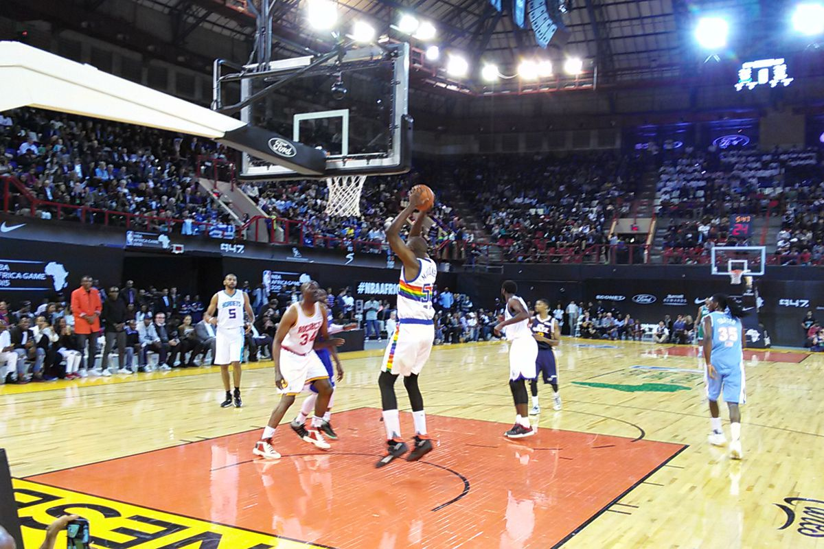 Nuggets legend Dikembe Mutombo doing what he does best, pulling down a rebound.
