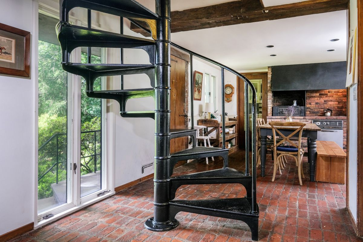 A black spiral staircase sits in front of the kitchen area on a brick floor.