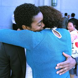 Jean Philippe Desius (left) hugs his wife, Marjorie Desius, both from Haiti, outside the Conference Center in Salt Lake City on April 5, 2015, after President Thomas S. Monson announced during the Sunday morning session of the 185th Annual General Conference of The Church of Jesus Christ of Latter-day Saints that a temple will be built in Haiti.