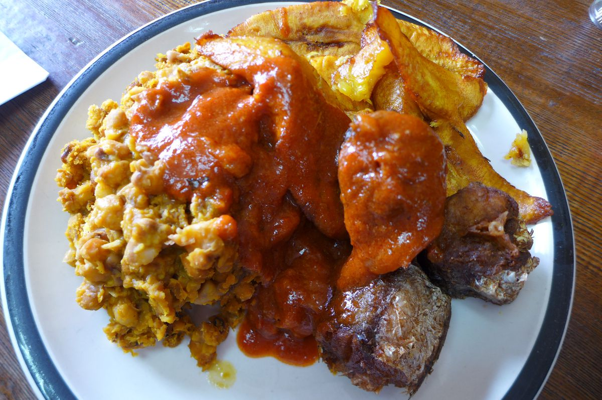 Fried plantains, fish, and stewed beans with red sauce.