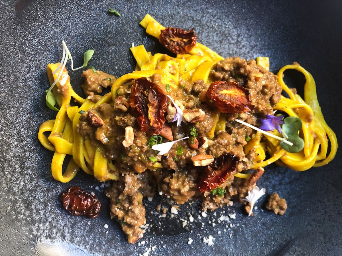 A very yellow pasta comes with garlic blossoms, olive oil powder, veal bolognese, and sundried tomatoes on a grey plate at Mucca
