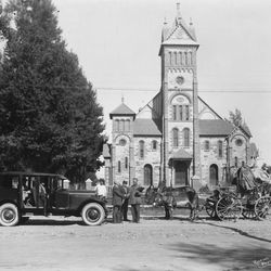 An automobile and wagon in front of the Bear Lake Tabernacle in Paris, Idaho, in the 1930s.