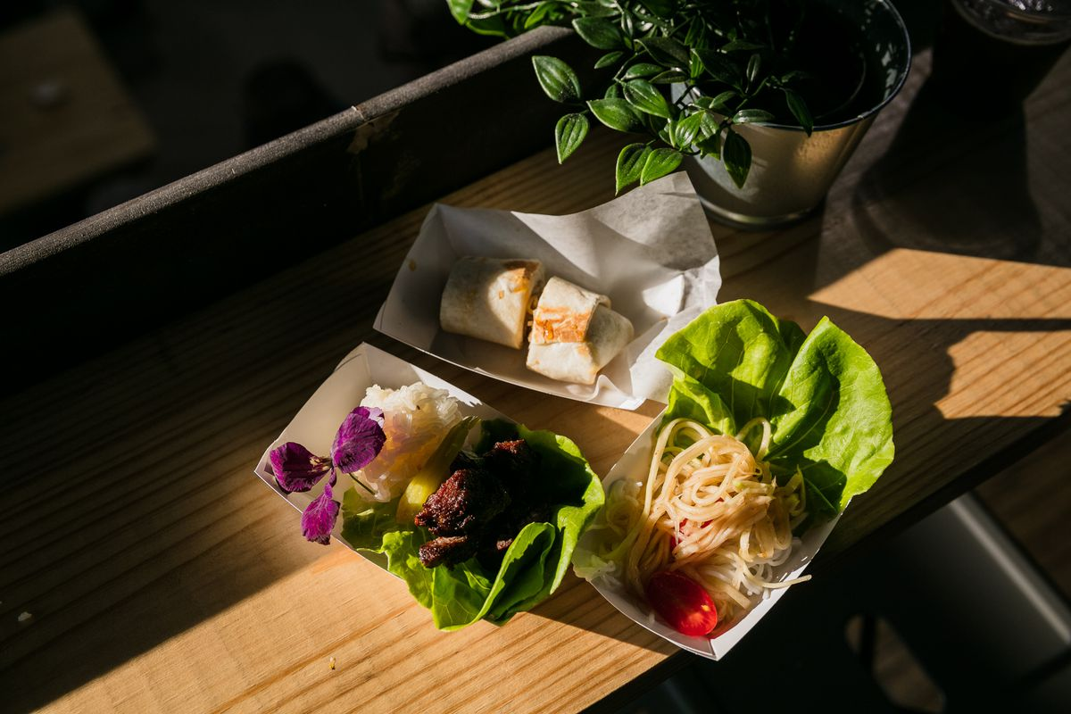pieces of candied beef with sticky rice, a papaya salad, and a spring roll sit in three paper boats on leaves of butter lettuce with a purple flower as garnish.