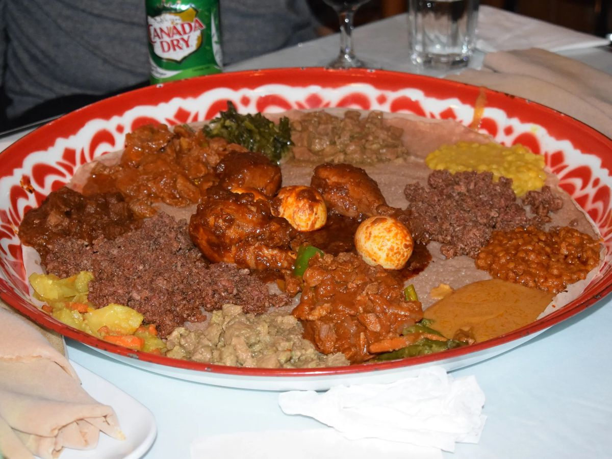 Doro wat on a red-rimmed plate