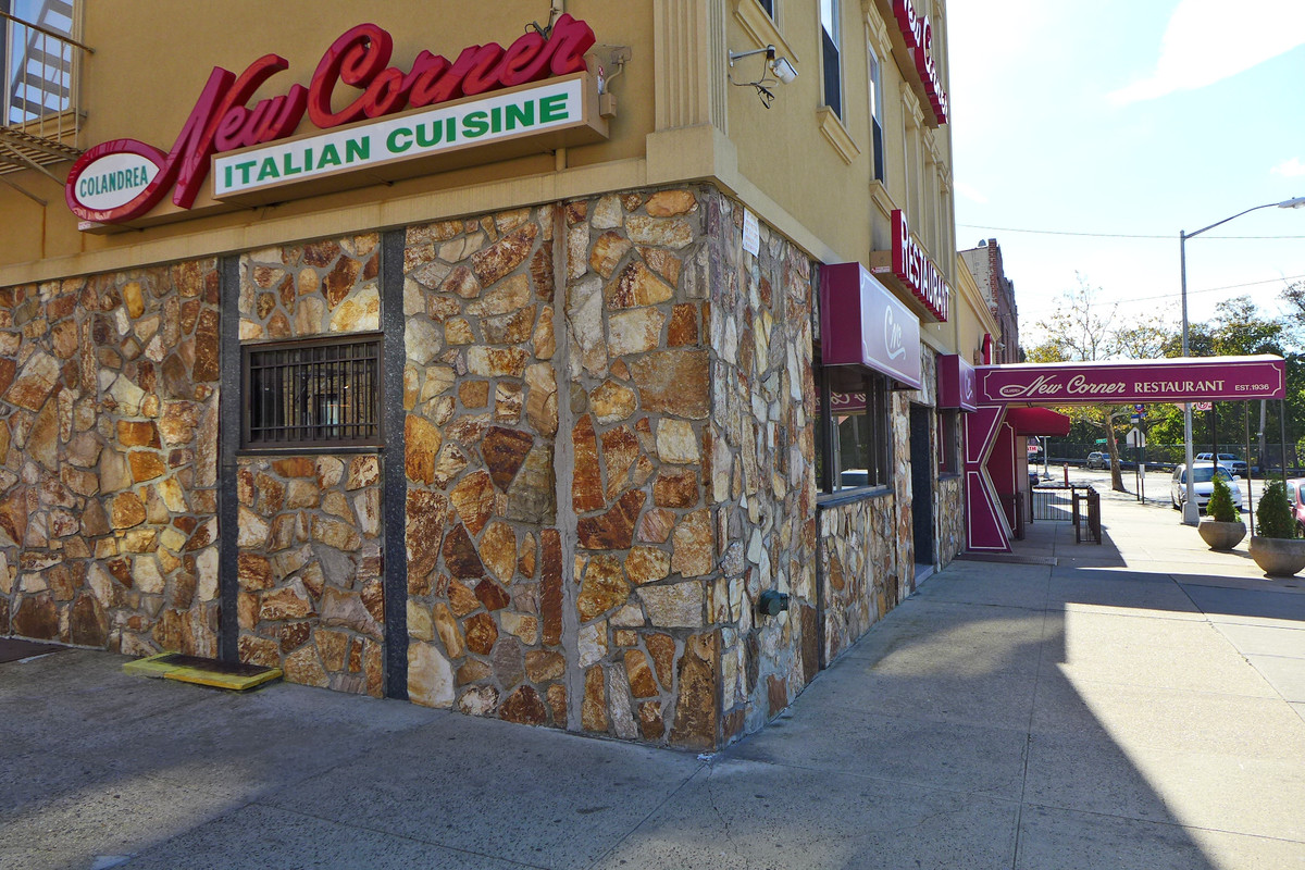 A tan facade of a restaurant with a big red sign spelling out the restaurant's name and a partial stone inlay on the building