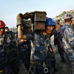 A Nepalese rescue worker carries the flight data recorder of a Sita Air airplane at the crash site near Katmandu, Nepal, early Friday, Sept. 28, 2012.  The plane carrying trekkers into the Everest region crashed just after takeoff Friday morning in Nepal's capital, killing all 19 people on board, authorities said.