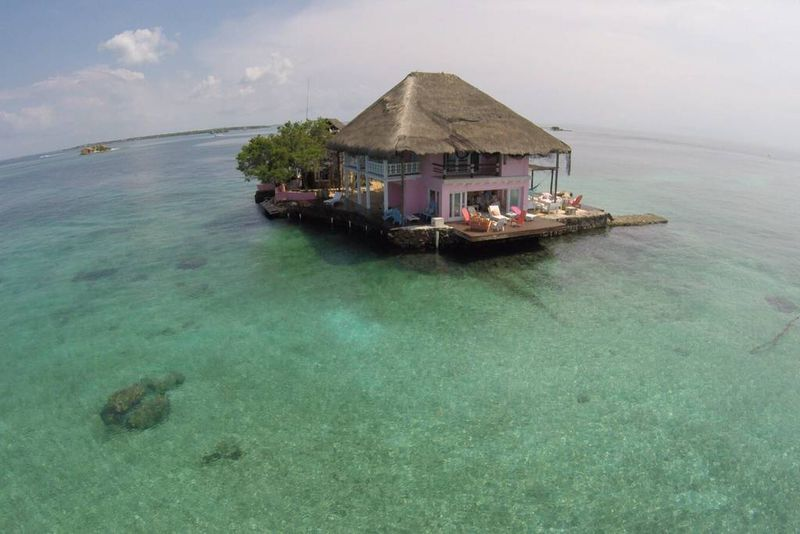 A pink house with a thatched roof sits in the middle of the ocean. A deck has lounge chairs and there are white clouds in the blue sky.