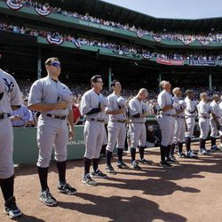 New York Yankees players stand for the national anthem in throw-back uniforms prior to a baseball game against the Boston Red Sox at Fenway Park in Boston, Friday, April 20, 2012, during a celebration of the 100th anniversary of the first regular-season game at the ball park.