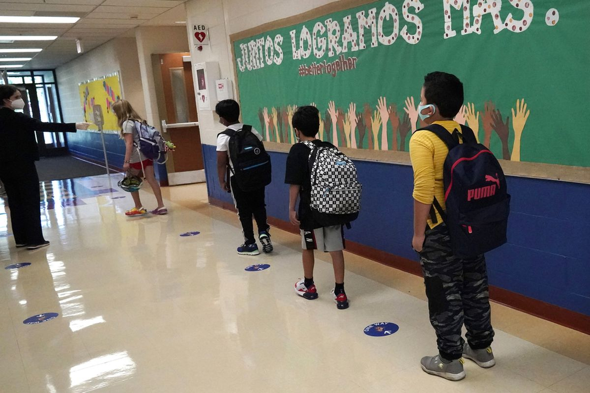 In this Sept. 3, 2020, file photo, students keep social distance as they walk to their classroom in Highwood, Ill.