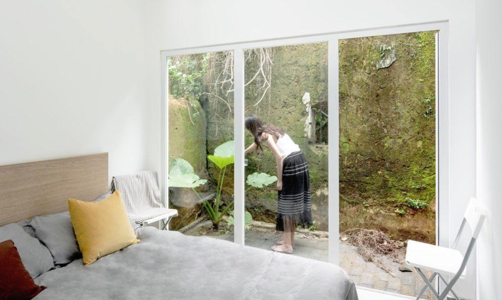 Woman watering plants outside of bedroom