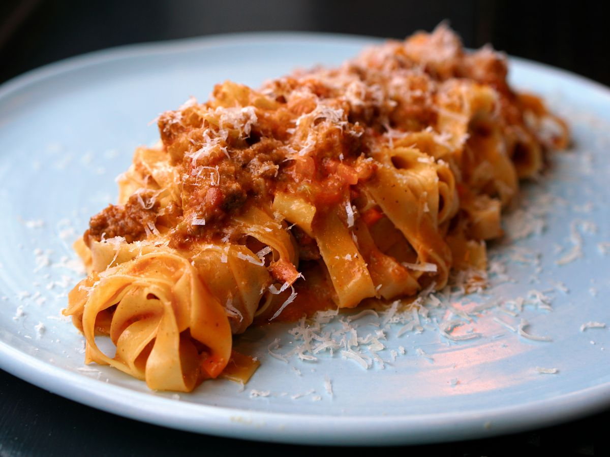 a white plate with a pile of noodles and red sauce