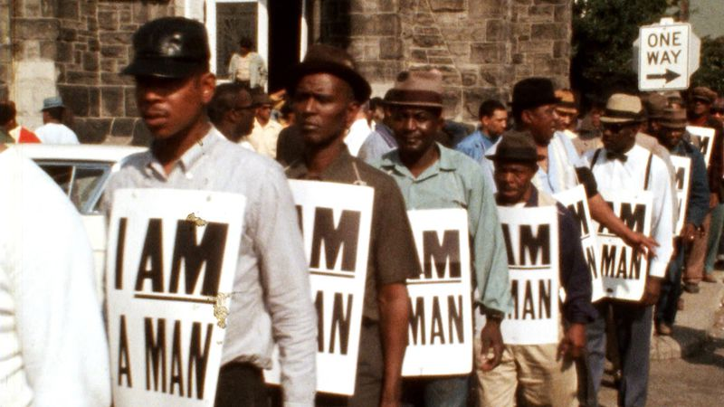"A line of Black men holding signs that read ""I Am a Man"" at a protest."