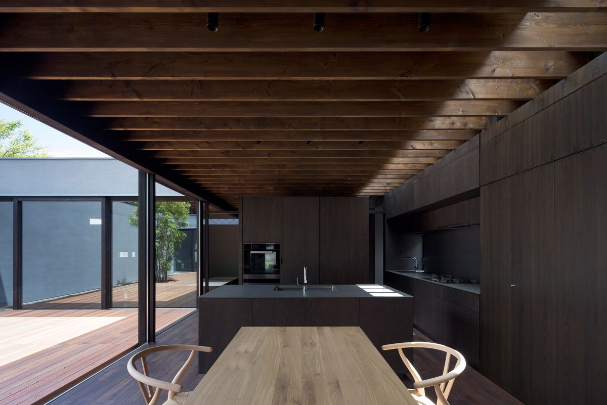 The dining area features a pale wood table and curved back seats. In the back is an all-black kitchen with an island and cabinetry.