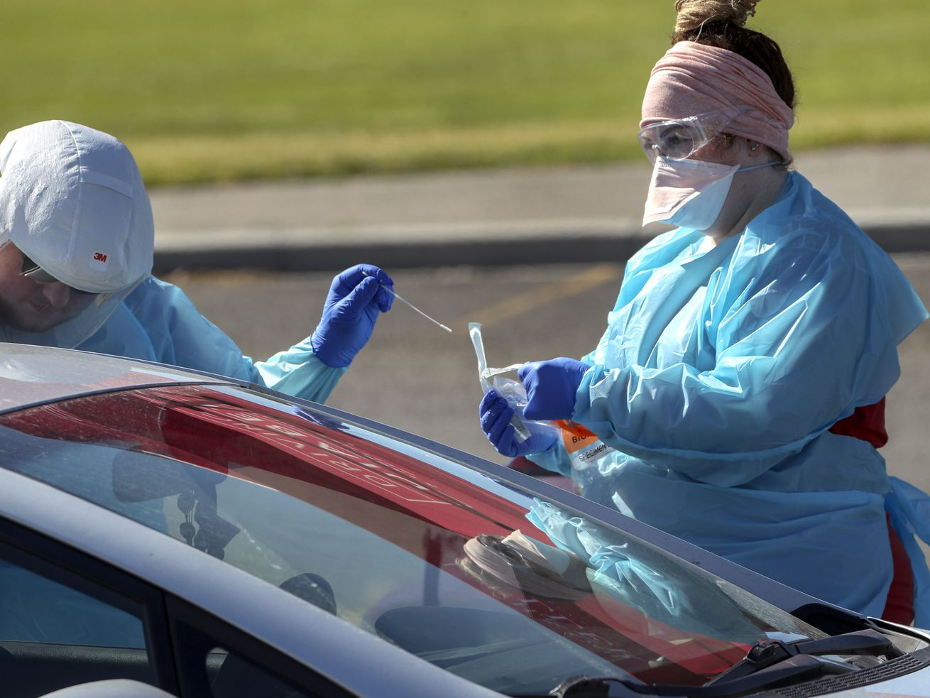 University of Utah Health's Dakota Silva, left, and Ashley Cameron work together as they test people for COVID-19 during the University of Utah's Wellness Bus drive-thru testing event at Centennial Park in West Valley City on Monday, July 6, 2020.