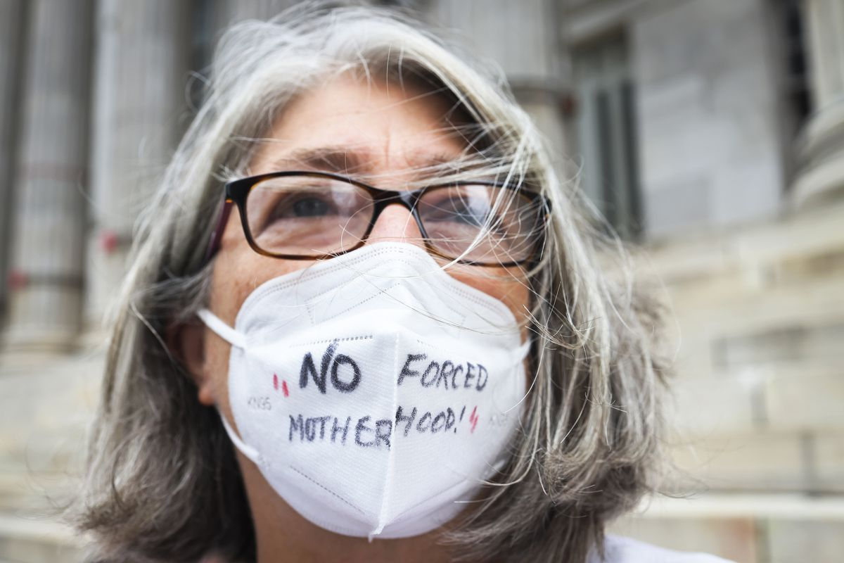 """A person wearing a breathing mask with the words """"no forced motherhood"""" written on it."""