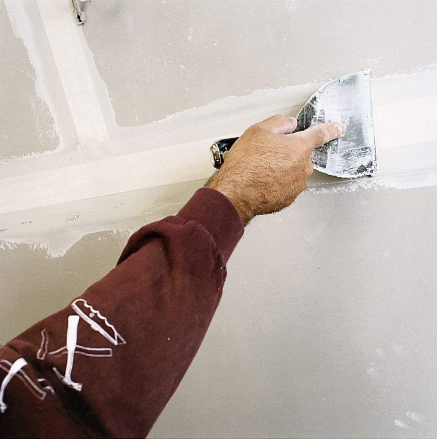 Man Smooths Drywall Tape Over With Compound