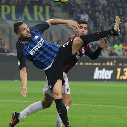 Danilo D'Ambrosio of FC Internazionale Milano competes for the ball with Andre Silva of AC Milan during the Serie A match between FC Internazionale and AC Milan at Stadio Giuseppe Meazza on October 15, 2017 in Milan, Italy.