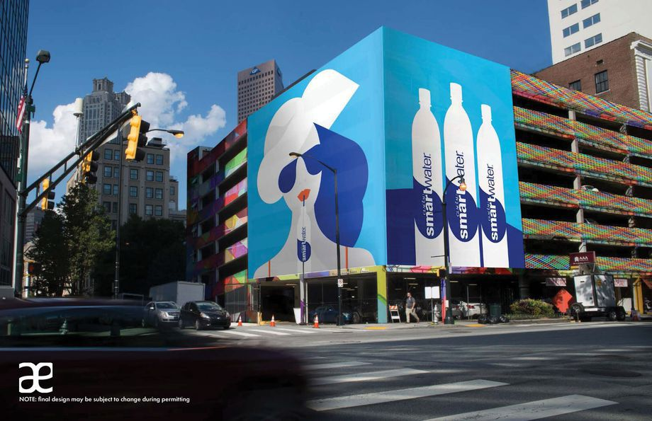 A parking deck with colorful painting on it and a huge LED billboard.