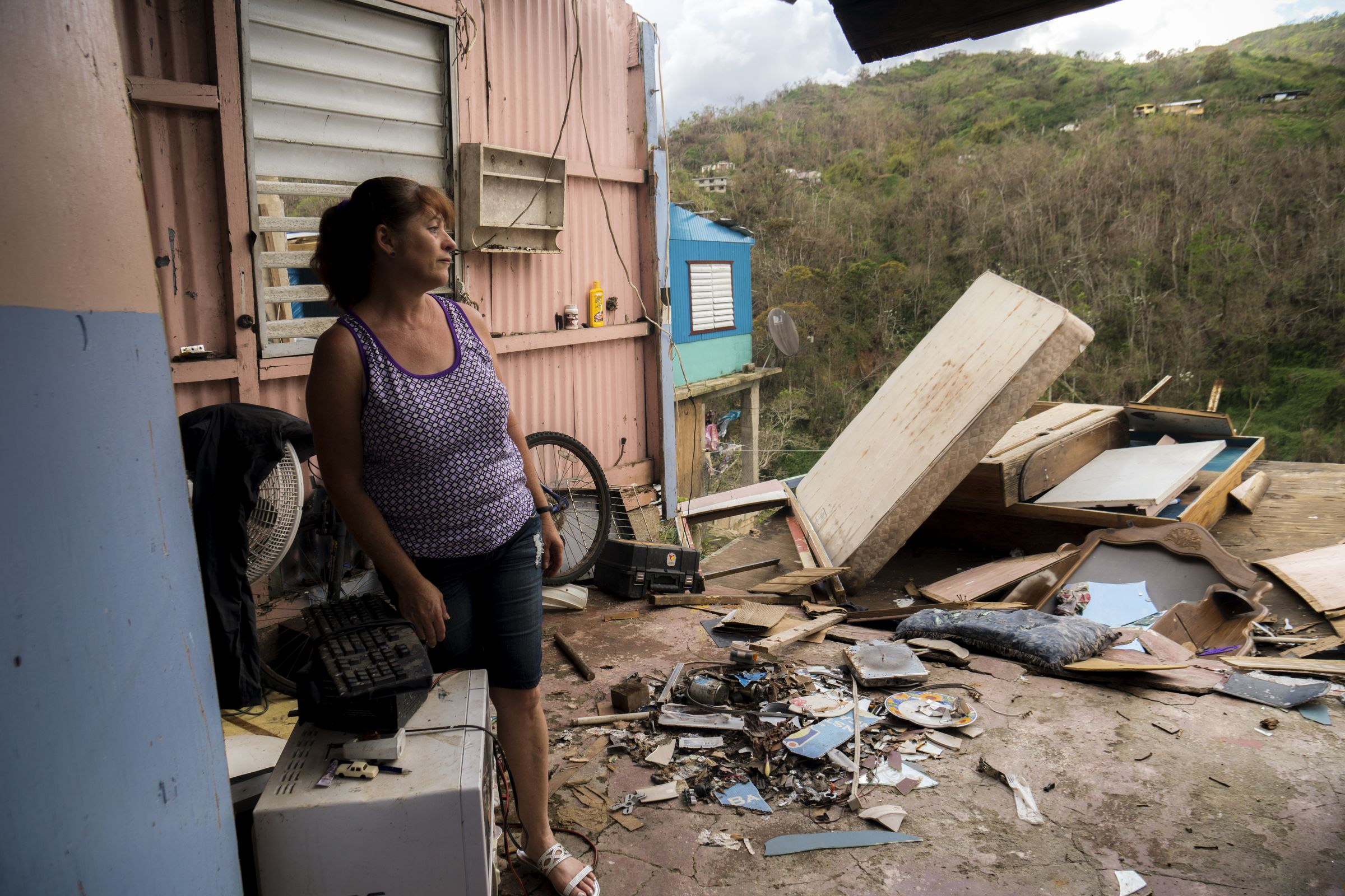 Rosana Aviles stands in the living room of her brother's hurricane destroyed house in the Juan Gonzalez neighborhood.