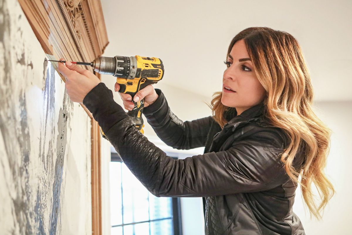 """Alison Victoria is pictured using a drill on a wall. The star of the show """"Windy City Rehab"""" is fighting back against a lawsuit filed by the buyers of a Bucktown home featured on the show."""