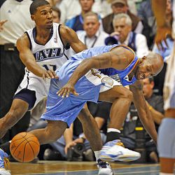 Denver's Chauncey Billups loses the ball as he is guarded by Utah's Ronnie Price as the Utah Jazz and the Denver Nuggets play.