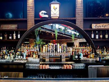 Fulton Hall's bar has a round mirror and is stocked with drinks.