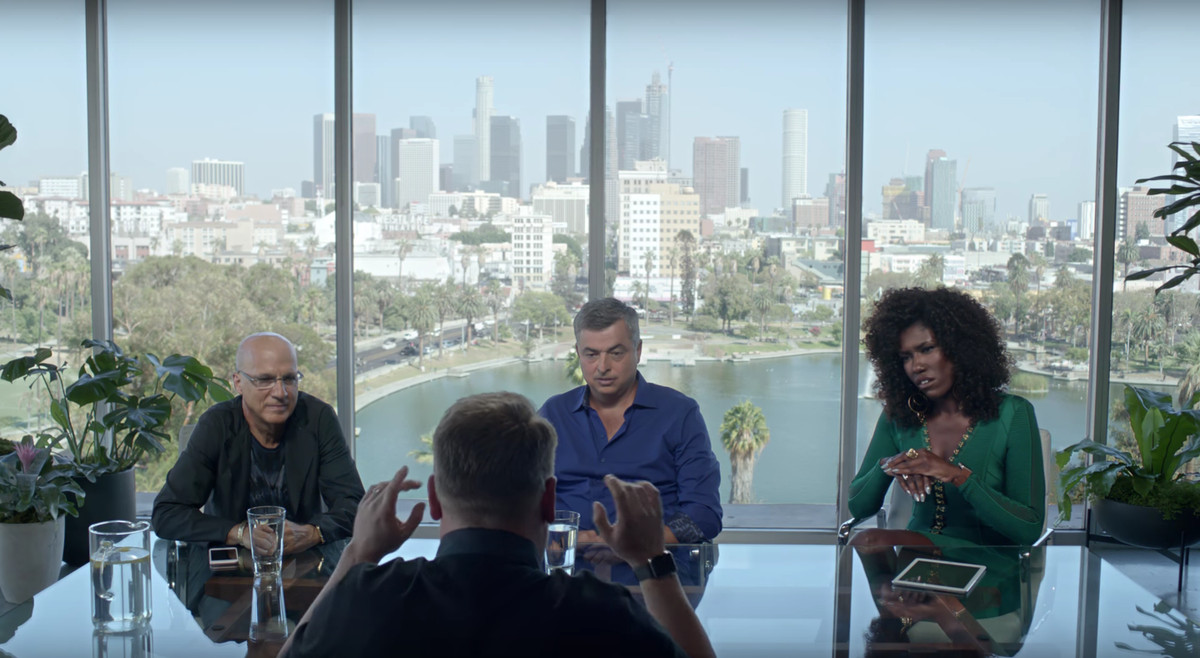The back of James Corden's head; he's facing three Apple executives at a table, Jimmy Iovine and Eddy Cue (both white men) and Bozoma Saint John (a black woman). Behind them is a picture window showing the Los Angeles skyline.