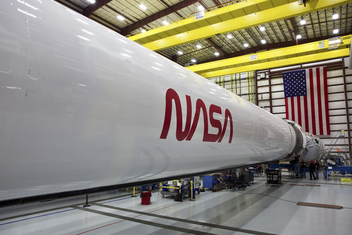 A rocket with the NASA logo on the side sits horizontal in a hangar.