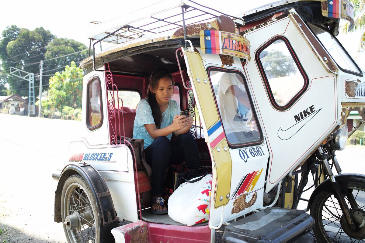 A woman inside a motorized pedicab looks at her mobile phone.