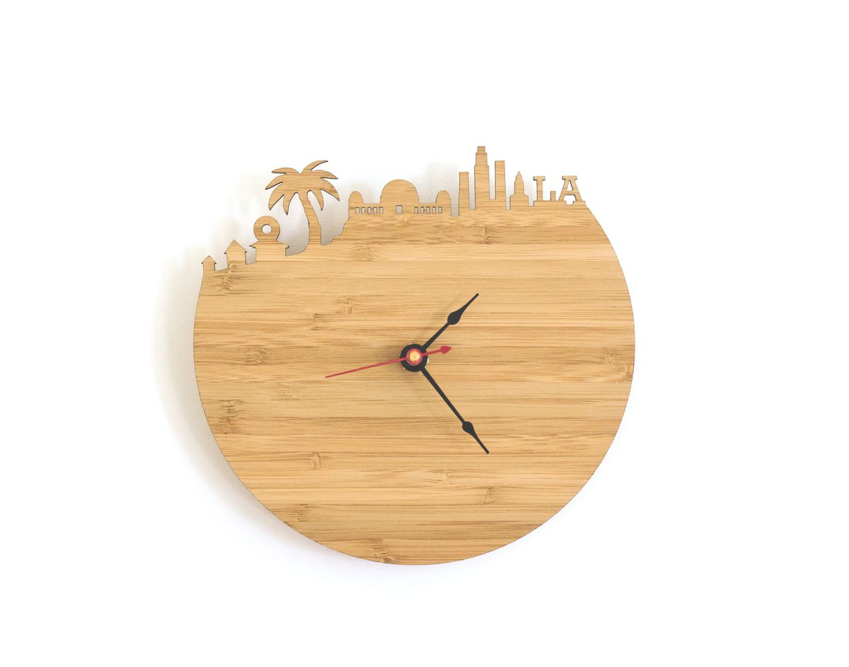 circular wood clock where the top is cut out in the shapes of LA landmarks