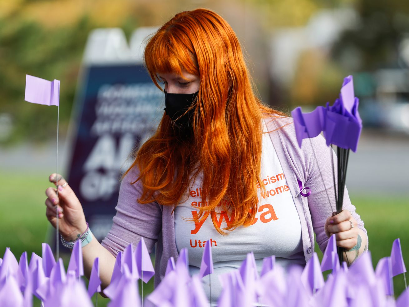 Christa Lynn Luckenbach plants a flag during a purple flag plating event at Liberty Park in Salt Lake City on Saturday, Oct. 17, 2020. The event was held by YWCA Utah to recognize the thousands of individuals in Utah who are impacted by domestic violence each year for the Stop the Violence Utah campaign.