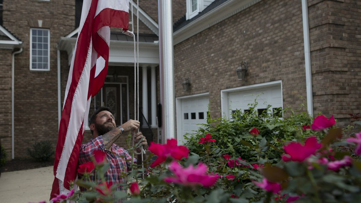 FBI Special Agent Jim Rudisill, a retired Army captain, takes down the flag at his Virginia home just before sunset. His successful legal battle could result in additional benefits for other long-serving veterans.