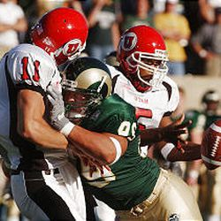 Utah quarterback Alex Smith (11) is hit hard by Colorado State's Patrick Goodpaster as he flips the ball to running back Brandon Warfield, right.