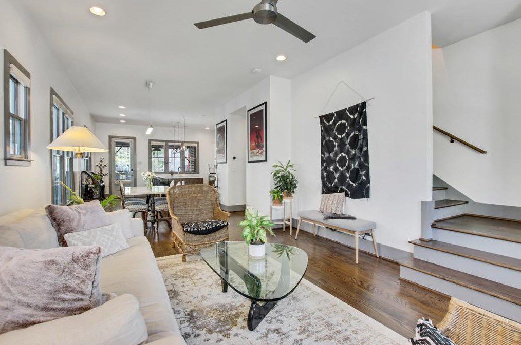 A long white room with a living room dining and kitchen,