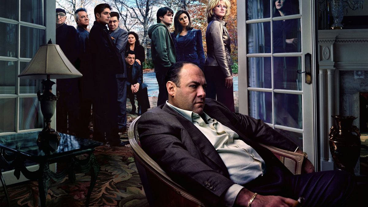 James Gandolfini as mob boss Tony Soprano sits slumped in a living-room chair, glowering offscreen, as his family and associates gather and watch him just outside his open patio doors.