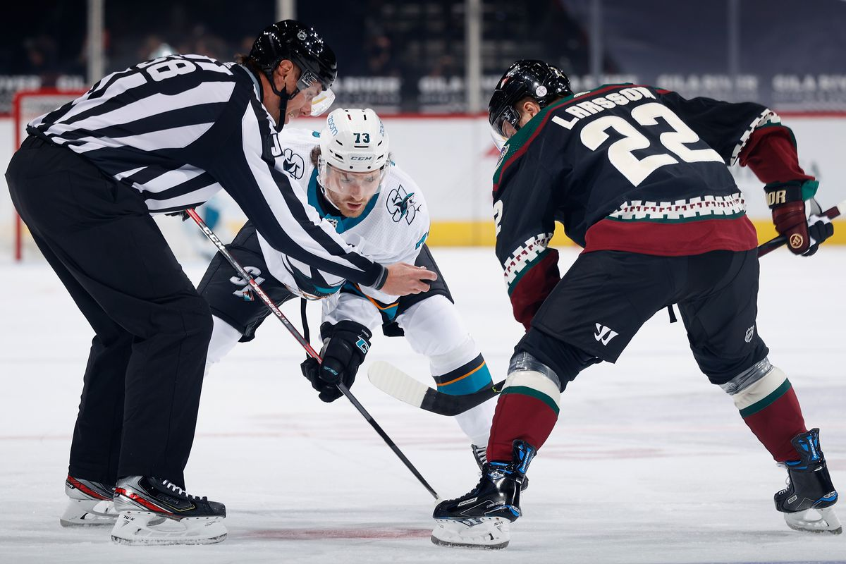 Noah Gregor #73 of the San Jose Sharks and Johan Larsson #22 of the Arizona Coyotes await a puck drop from linesman Ryan Gibbons #58 during the NHL game at Gila River Arena on January 14, 2021 in Glendale, Arizona. The Sharks defeated the Coyotes 4-3 in an overtime shoot-out.