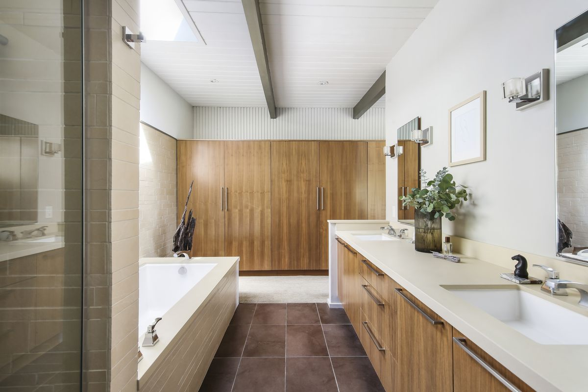 A bathroom with a tub, two sinks, and back wall of wooden closets.