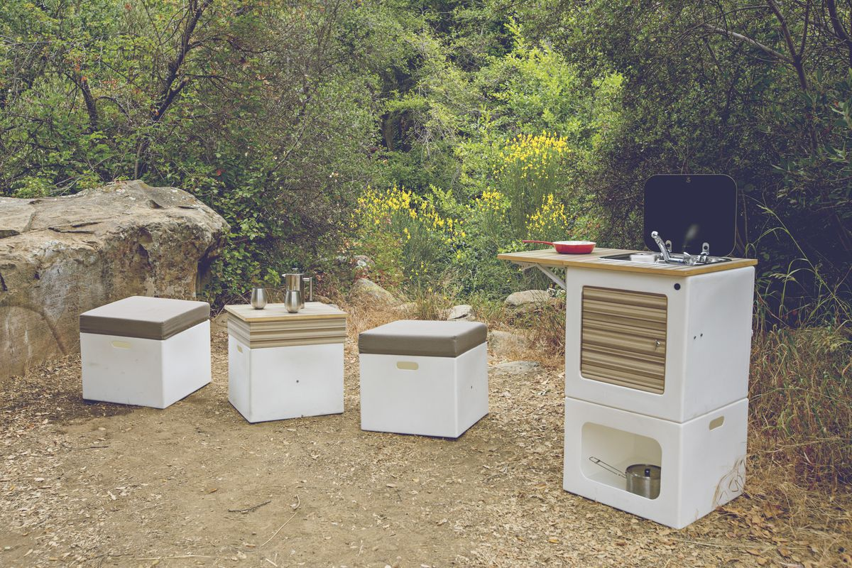 White cubes with sunbrella fabric outside as seating next to an outdoor kitchen.