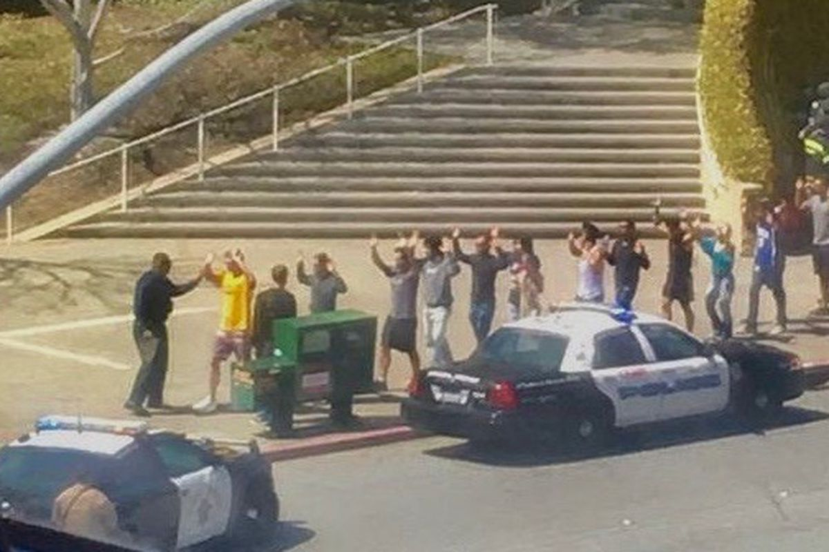 YouTube employees walk with their hands up past a police car.