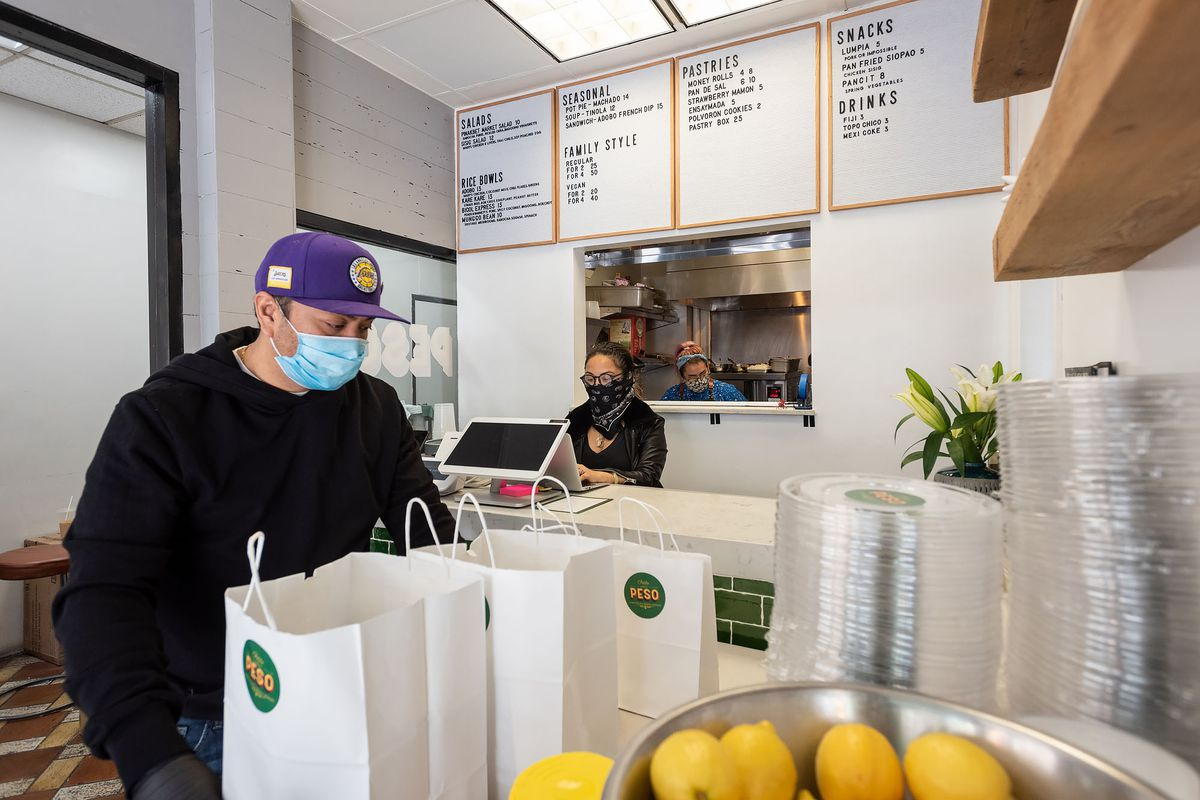 A masked worker in a purple hat handles food for delivery.