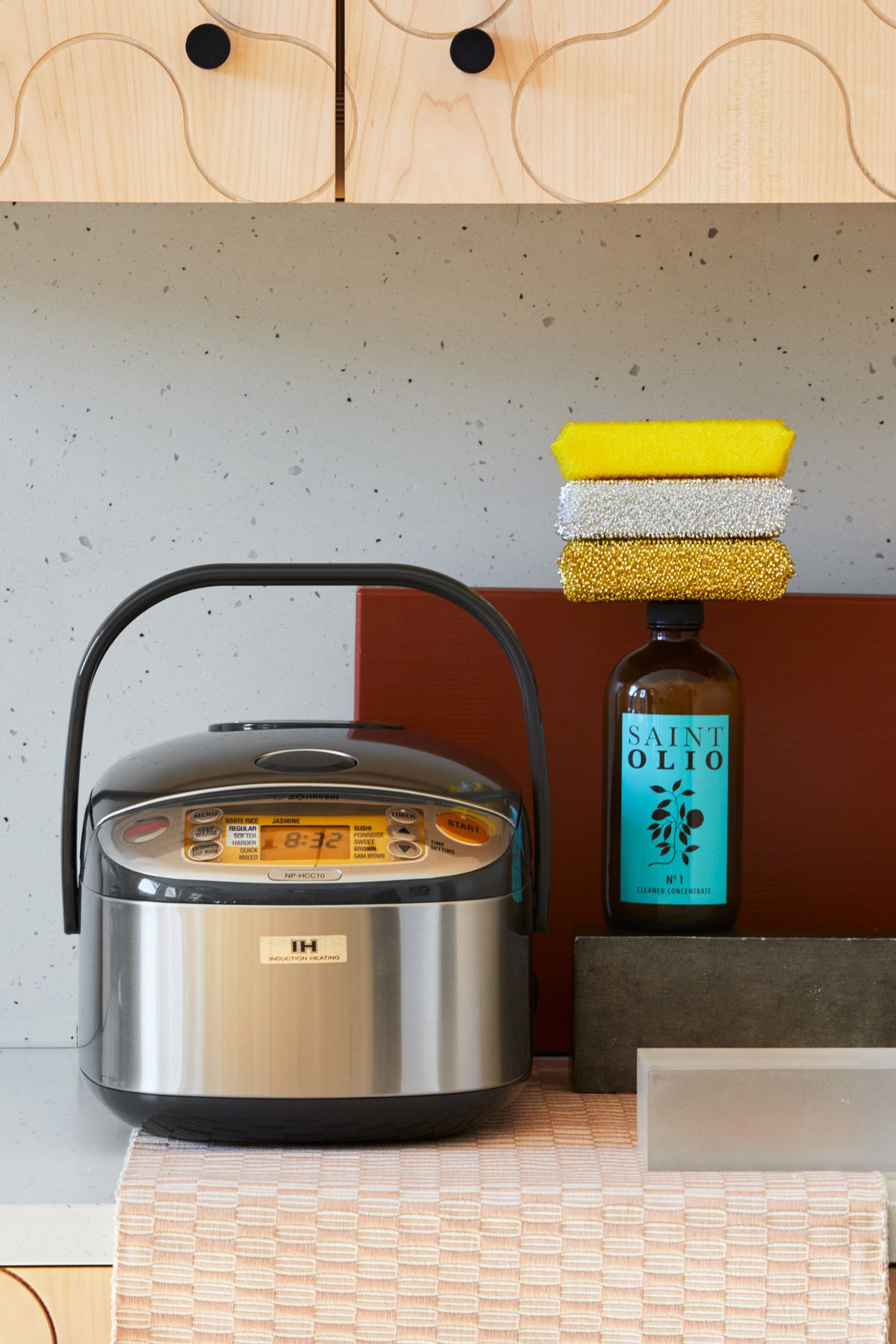 A rice booker, cleaner and a stack of sponges in a kitchen.