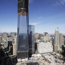 """FILE- In this April 17, 2012, file photo, One World Trade Center,  rises above the lower Manhattan skyline and the National September 11 Memorial, lower right, in New York. One World Trade Center, the giant monolith being built to replace the twin towers destroyed in the Sept. 11 attacks, will lay claim to the title of New York City's tallest skyscraper on Monday, April 30, as workers erect steel columns that will make its unfinished skeleton a little over 1,250 feet, just high enough to peak over the observation deck on the Empire State Building. The milestone is a preliminary one. The so-called """"Freedom Tower"""" isn't expected to reach its full height for at least another year, at which point it is likely to be declared the tallest building in the U.S."""