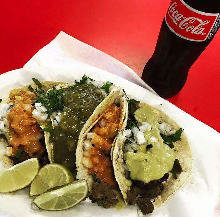 Four tacos, topped with salsas and cilantro, along with lime wedges on a paper plate beside a glass bottle of Coke